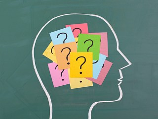 Brain with colorful critical thinking question marks