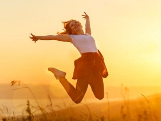 Woman jumping with joy at sunset