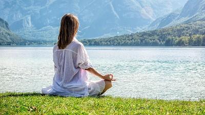 Woman meditating by the lake
